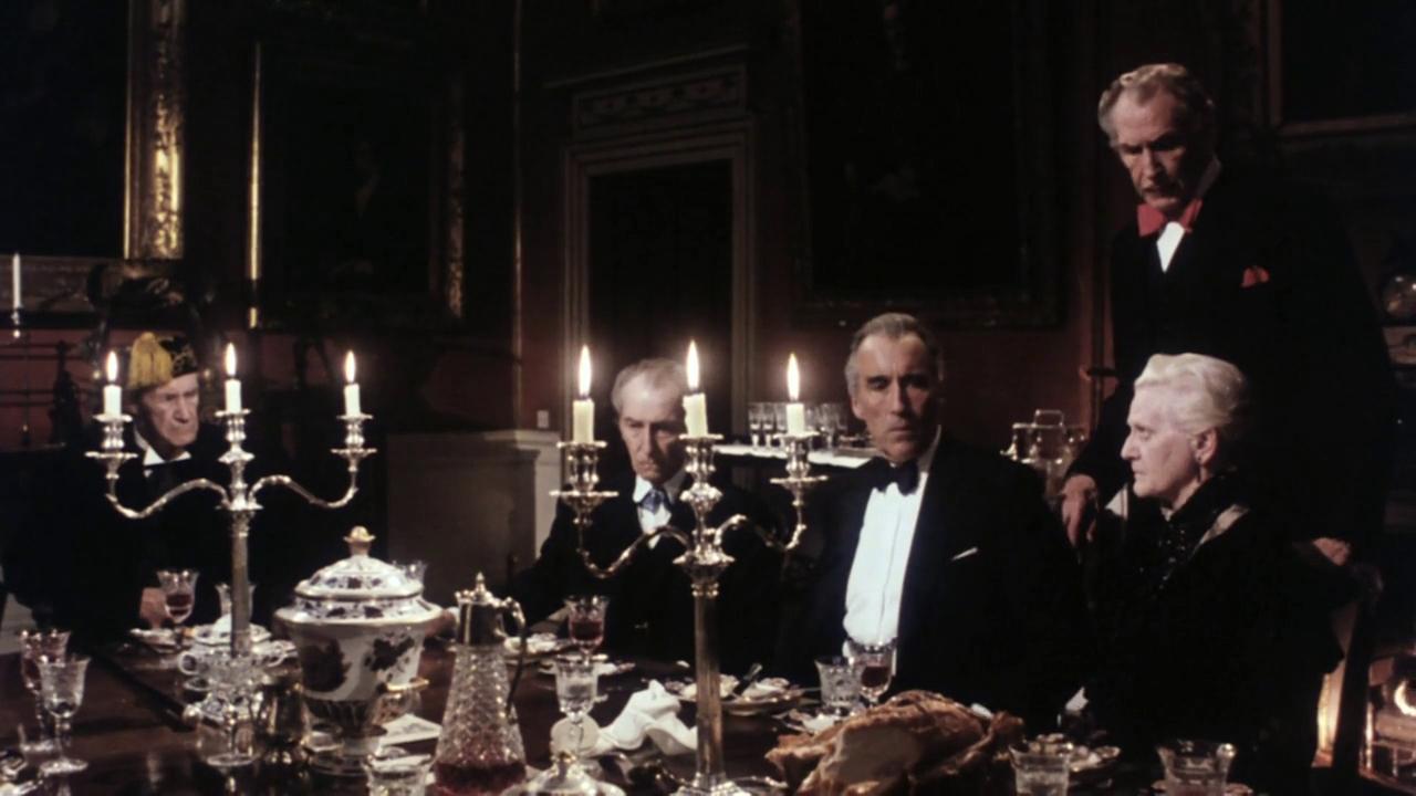 Am gedeckten Tisch zu Kerzenlicht sitzt Christopher Lee mit seinen alternden Kollegen