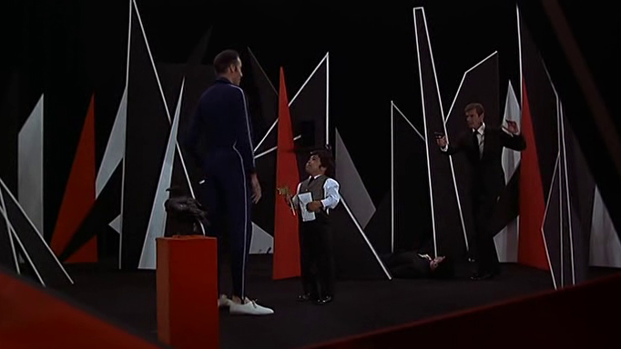 Scaramanga und Nick Nack stehen im Trainingsparcour des Killers. Im Hintergrund ein Puppenaufsteller von James Bond.