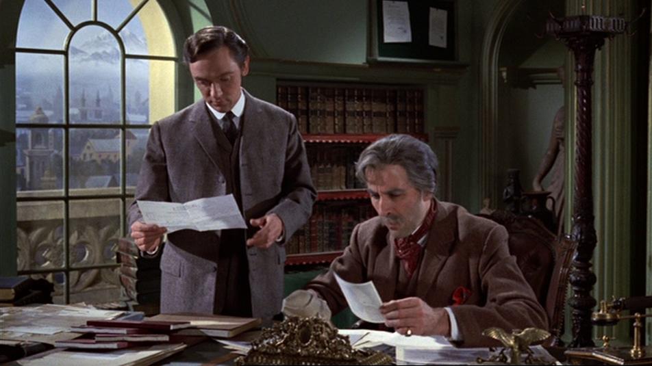 Lee sitzt als Prof. Meister am Schreibtisch und studiert mit seinem Kollegen einen Brief.
